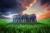 Business people standing up against green field under orange sky