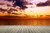 An illustration of a bright ocean sunset with a wooden jetty foreground