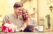 summer holidays, city, dating and technology concept - couple with tablet pc in cafe