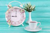 foto of analog clock  - Beautiful vintage alarm clock with flowers and cup of tea on blue wooden background - JPG