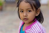 Sucre, Bolivia - January 17, 2012: A Young Girl Faces The Camera While Playing In The Street. Januar