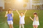 stock photo of fountain grass  - Happy kids has fun playing in water fountains - JPG