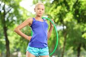 Female athlete on a mat holding a hula hoop in a park
