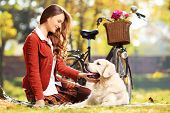 Beautiful female sitting on a grass and looking at her labrador retriever dog in a park