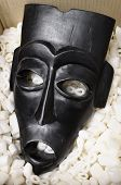 stock photo of african mask  - Black African mask packed in polystyrene pieces and cardboard - JPG