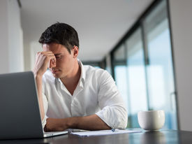 stock photo of fail job  - frustrated with problems young business man working on laptop computer at home - JPG