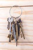 Many old keys on a wooden background.