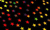 Festive starry background, many little colorful stars on black backdrop, beautiful Christmas decoration, festive wrapping paper