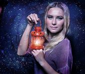 Closeup portrait of cute blond female holding in hands red antique lantern, festive starry night, Christmas celebration concept