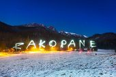 Zakopane sign under Tatra mountains at night, Poland