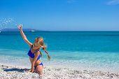 Adorable little girl making leg-split on tropical white sandy beach and enjoying summer vacation