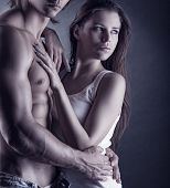 image of foreplay  - Young beautiful loving couple is embracing on a dark background - JPG