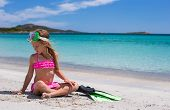 stock photo of flipper  - Little girl with flippers and goggles for swimming on the beach - JPG