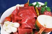 uncooked fresh beef meat chunks on white bowls with vegetables and red peppers serving on blue table with cutlery