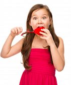 Portrait of little girl is biting a red heart, isolated over white