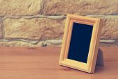 old photo frame on the wooden table, retro film filtered, instagram style