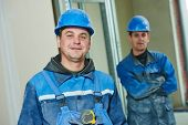 cheerful plasterboard workers team at a indoors wall insulation works
