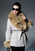portrait of fashion model in fur coat clothes with sunglasses posing in studio
