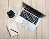 Open notebook and crumbled diary papers with saucer of candies on wooden background, top view