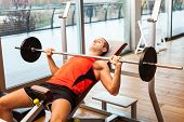 picture of lifting weight  - Man lifting a weight in a fitness club - JPG