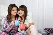 Beautiful girls twins in pajamas drinking tea at home