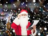 christmas, holidays and people concept - man in costume of santa claus with notepad over snowy night city background