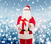 christmas, holidays and people concept - man in costume of santa claus with gift box over snowy city background