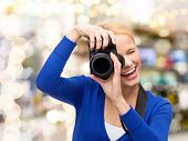photography, technology, holidays, and people concept - smiling young woman taking picture with digital camera over lights background