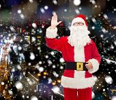 christmas, holidays, gesture and people concept - man in costume of santa claus waving hand over snowy night city background
