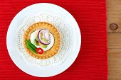Tartlet with greens and vegetables with sauce on plate on table
