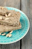 Sunflower halva with peanuts on plate, on wooden background