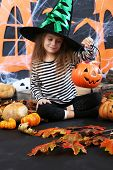 Little girl in hat asks candy on Halloween decorations background