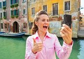 Happy Young Woman Showing Thumbs Up And Making Selfie In Venice,