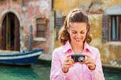 Happy Young Woman Checking Photos In Camera In Venice, Italy