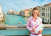 picture of piccolo  - Portrait of happy young woman with map standing on bridge with grand canal view in venice italy - JPG