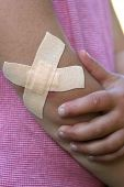 Sore elbow with plasters in a cross
