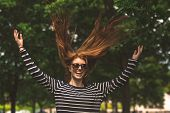 Portrait of beautiful young woman jumping in the park