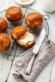 Homemade Buns With Raisins On Wire Cooling Rack On Blue Wooden Background