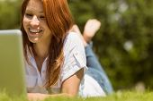 Pretty redhead happy and lying with her laptop on grass in park