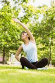 Full length of healthy and beautiful young woman stretching hand in park