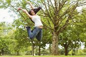 Excited and happy brunette jumping in the park