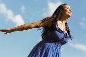 Pretty brunette in blue dress feeling free on a sunny day