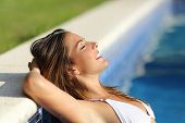 image of rest-in-peace  - Side view of a happy woman relaxed in a swimming pool enjoying vacations with a green and blue background - JPG