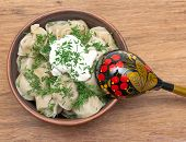 Russian Dumplings In A Clay Bowl With Sour Cream And Dill On A Wooden Background