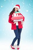 Festive brunette in santa hat and red coat holding pile of gifts against blue background with vignette