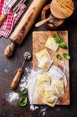 Raw Homemade Ravioli With Pasta Cutter On Dark Wooden Background