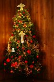 Decorated Christmas tree  on wooden wall background