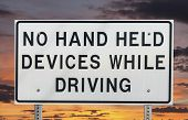 No hand held devices while driving sign isolated with sunset sky.