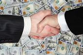 stock photo of two dollar bill  - Handshake of two business men in suits on the background of hundred dollar bills stacked side by side in a random order - JPG