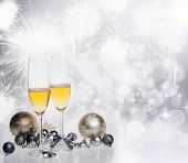 Toasting with two champagne glasses against holiday lights, fireworks and clock close to midnight